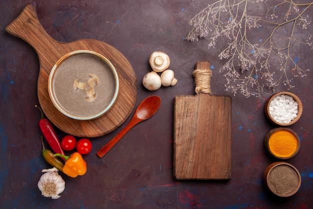 Bovenaanzicht smakelijke champignonsoep met verschillende kruiden op het donkere bureau soep champignons kruiden voedsel maaltijd
