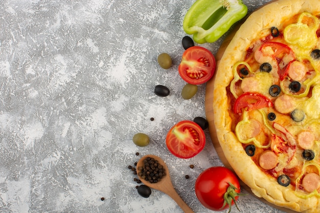 Bovenaanzicht smakelijke cheesy pizza met olijven worstjes en rode tomaten op de grijze achtergrond fastfood italiaanse deegmaaltijd