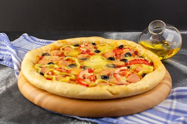 Bovenaanzicht smakelijke cheesy pizza met rode tomaten, zwarte olijven en worst met olie op de donkere achtergrond fast-food maaltijd italiaans deeg