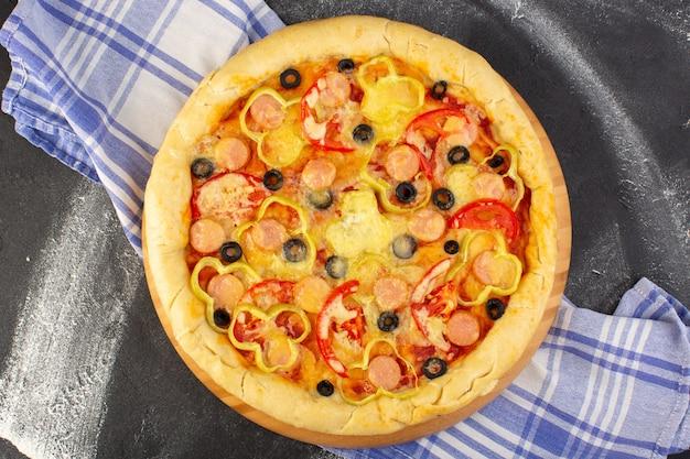 Bovenaanzicht smakelijke cheesy pizza met rode tomaten, zwarte olijven en worst op de donkere achtergrond met handdoek fast-food maaltijd italiaans deeg