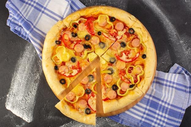 Bovenaanzicht smakelijke cheesy pizza met rode tomaten, zwarte olijven en worst op de donkere achtergrond met handdoek fastfood italiaans deeg