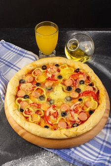 Bovenaanzicht smakelijke cheesy pizza met rode tomaten, zwarte olijven en worstjes met sapolie op de donkere achtergrond fastfood italiaans deeg
