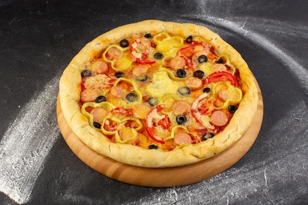 Bovenaanzicht smakelijke cheesy pizza met rode tomaten, zwarte olijven en worstjes op de donkere achtergrond fast-food maaltijd italiaans deeg