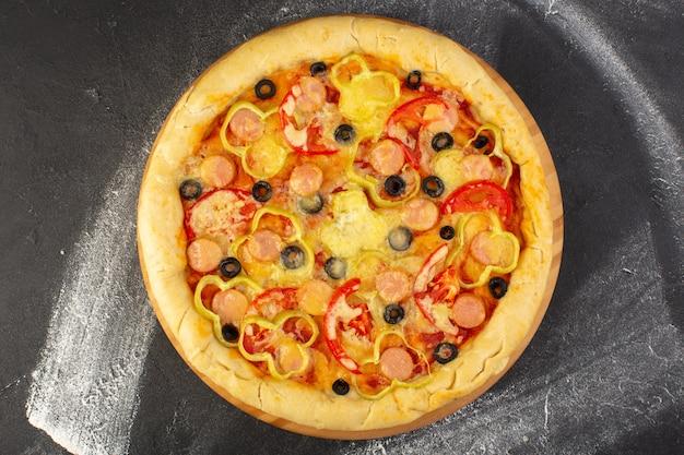 Bovenaanzicht smakelijke cheesy pizza met rode tomaten, zwarte olijven en worstjes op de donkere achtergrond fastfood italiaans deeg
