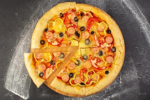 Bovenaanzicht smakelijke cheesy pizza met rode tomaten, zwarte olijven, paprika en worstjes op de donkere achtergrond fastfood italiaans deeg