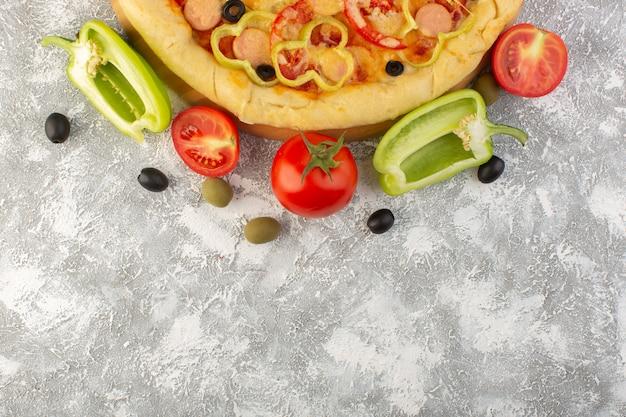 Bovenaanzicht smakelijke cheesy pizza met zwarte olijven worstjes en rode tomaten op de grijze achtergrond fastfood italiaanse deeg maaltijd bakken voedsel