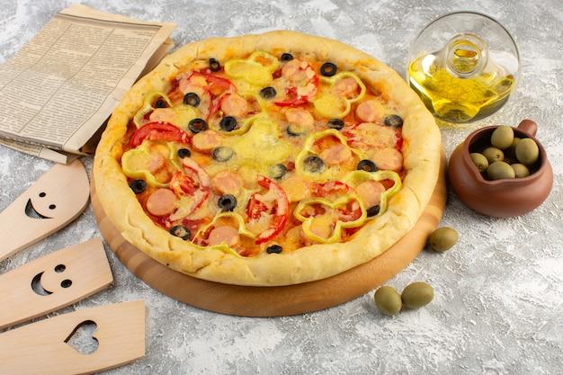 Bovenaanzicht smakelijke cheesy pizza met zwarte olijven worstjes en rode tomaten samen met olie en olijven op de grijze achtergrond fast-food italiaans deeg maaltijd bakken
