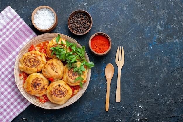 Bovenaanzicht smakelijke deegmaaltijd met vlees in plaat samen met kruidenlepel en vork op de donkere groente van het de maaltijdvlees van het bureauvoedsel