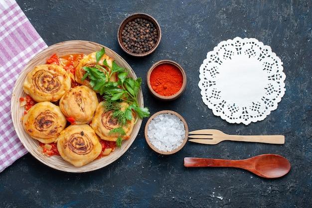 Bovenaanzicht smakelijke deegmaaltijd met vlees in plaat samen met kruidenlepel op de donkere groente van het de maaltijdvlees van het bureauvoedsel