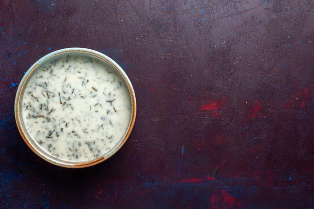 Bovenaanzicht smakelijke dovga van yoghurt met greens binnen op de donkere tafel, maaltijd eten soep groen diner