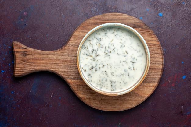 Bovenaanzicht smakelijke dovga van yoghurt met greens binnen op de donkere tafel, maaltijdsoep groen