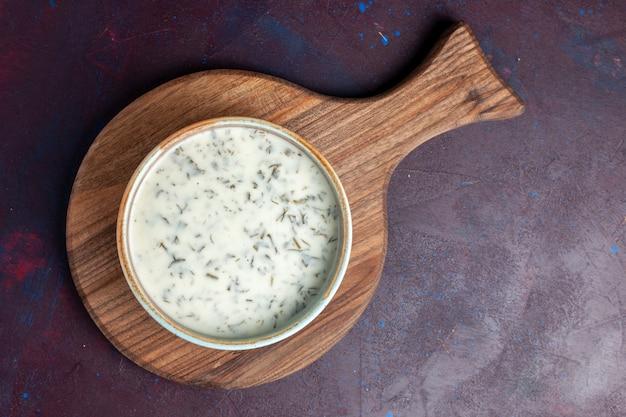 Bovenaanzicht smakelijke dovga van yoghurt met greens binnen op de donkere tafel
