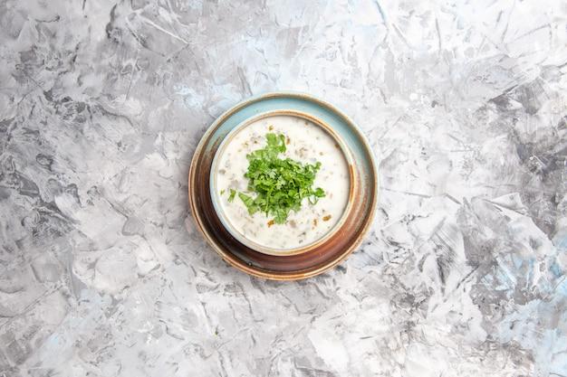 Bovenaanzicht smakelijke dovga yoghurtsoep met greens in plaat op witte tafel melksoepmaaltijd