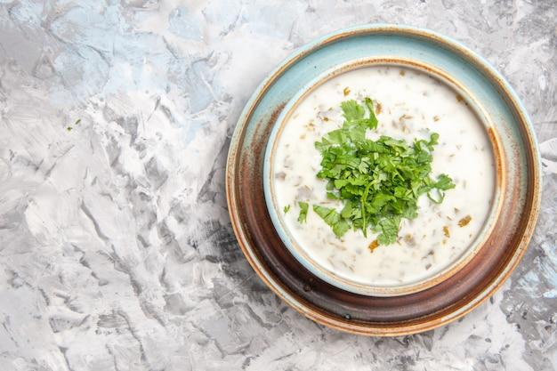 Bovenaanzicht smakelijke dovga yoghurtsoep met greens op de witte tafel melk soep maaltijdschotel