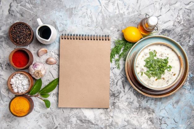 Bovenaanzicht smakelijke dovga yoghurtsoep met greens op witte tafel melksoepschotel
