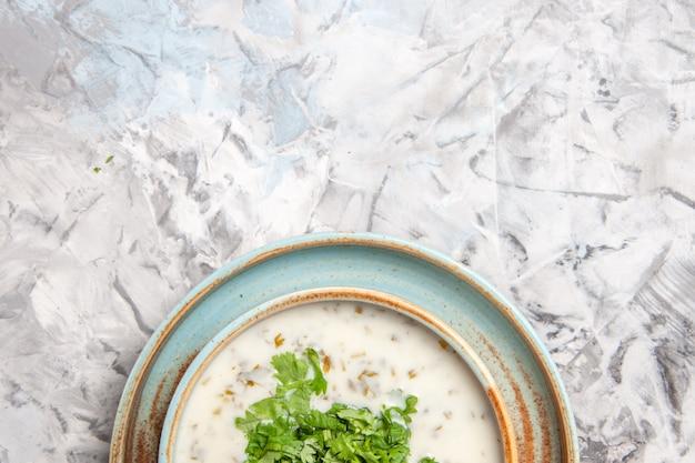 Bovenaanzicht smakelijke dovga yoghurtsoep met greens op witte tafelmelkmaaltijdschotel