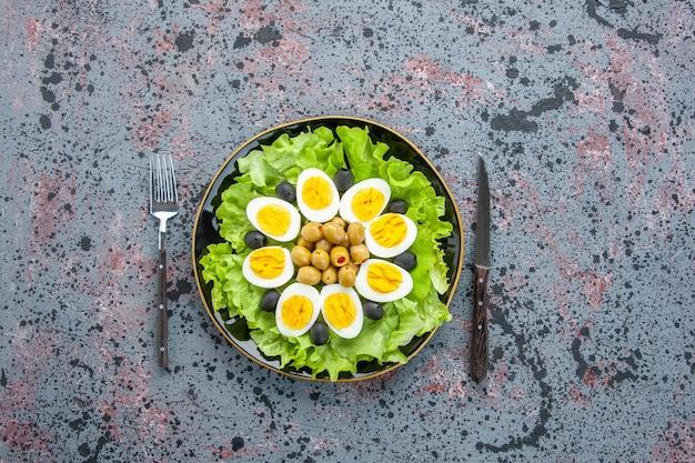 Bovenaanzicht smakelijke eiersalade bestaat uit groene salade en olijven op lichte achtergrond