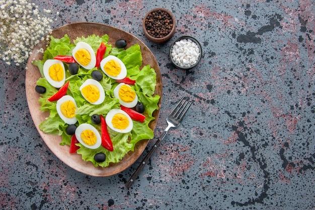 Bovenaanzicht smakelijke eiersalade met groene salade en olijven op lichte achtergrond