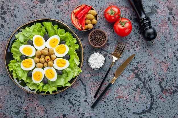 Bovenaanzicht smakelijke eiersalade met kruiden en olijven op lichte achtergrond