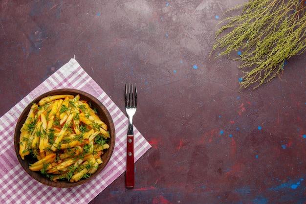 Bovenaanzicht smakelijke frietjes met groen op het donkere oppervlak