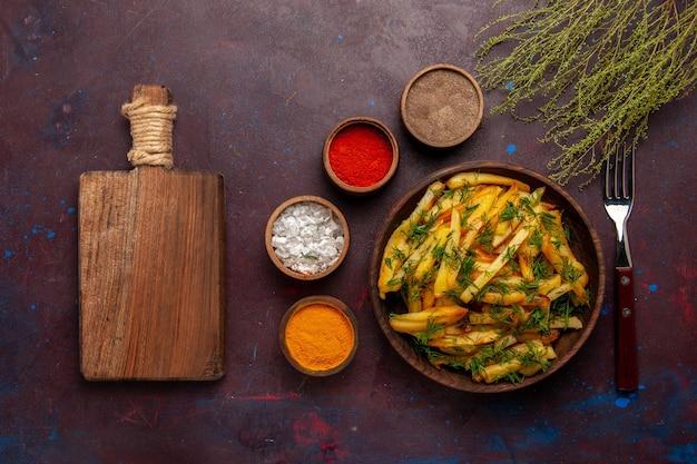 Bovenaanzicht smakelijke frietjes met groenten en verschillende smaakmakers op het donkere oppervlak