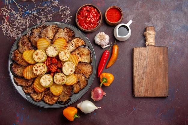 Bovenaanzicht smakelijke gebakken groenten aardappelen en aubergines op de donkere achtergrond maaltijd oven koken bak groente