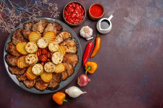 Bovenaanzicht smakelijke gebakken groenten aardappelen en aubergines op de donkere achtergrond maaltijd oven koken bakken groenten