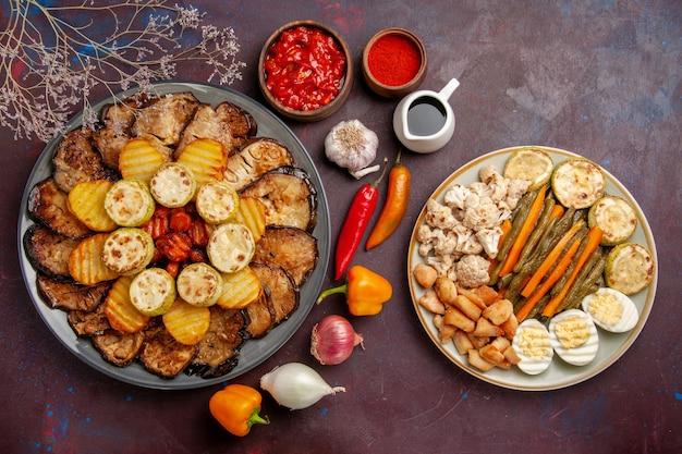 Bovenaanzicht smakelijke gebakken groenten aardappelen en aubergines op donkere achtergrond maaltijd oven koken bak plantaardige kleur