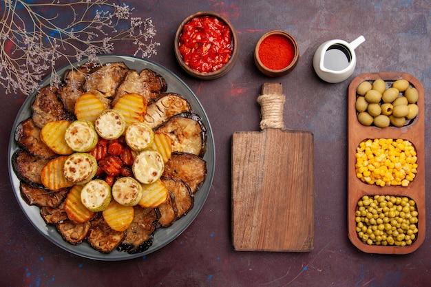 Bovenaanzicht smakelijke gebakken groenten aardappelen en aubergines op donkere bureau maaltijd oven koken bakken groenten