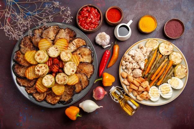 Bovenaanzicht smakelijke gebakken groenten met eiermeel en kruiden op donkere achtergrond maaltijd oven koken bak plantaardige kleur