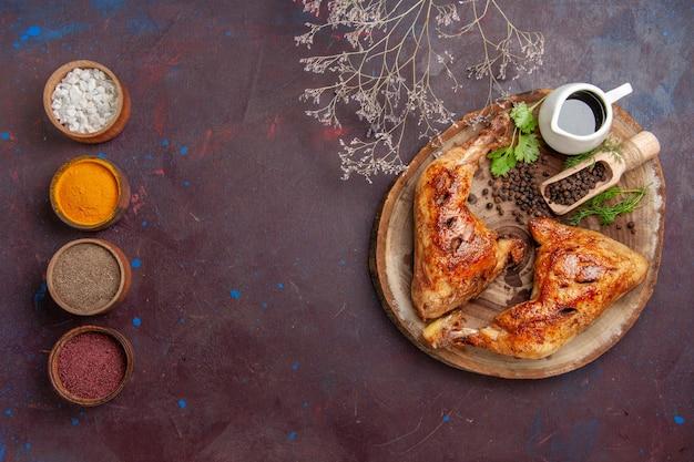Bovenaanzicht smakelijke gebakken kip met kruiden op donkere achtergrond voedsel kippenmeel plantaardig vlees