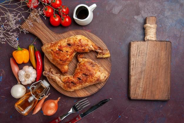Bovenaanzicht smakelijke gebakken kip met verse groenten en kruiden op het donkere bureau