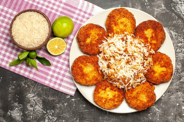 Bovenaanzicht smakelijke gebakken koteletten met gekookte rijst op een donkere ondergrond rissole vlees eten