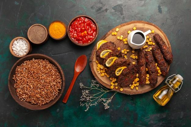 Bovenaanzicht smakelijke gebakken schnitzels met boekweit en verschillende kruiden op donkergroene achtergrond