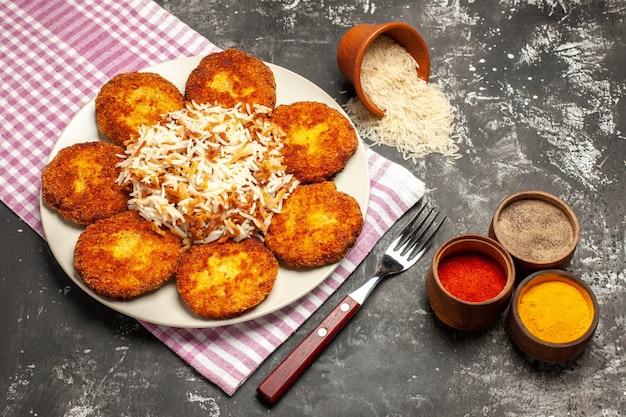 Bovenaanzicht smakelijke gebakken schnitzels met gekookte rijst op donker oppervlak rissole vlees