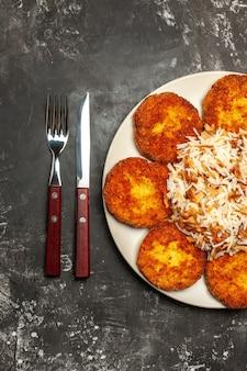 Bovenaanzicht smakelijke gebakken schnitzels met gekookte rijst op donkere ondergrond gerecht maaltijd foto vlees