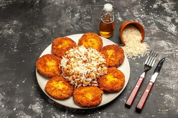 Bovenaanzicht smakelijke gebakken schnitzels met gekookte rijst op donkere oppervlak gerecht maaltijd foto