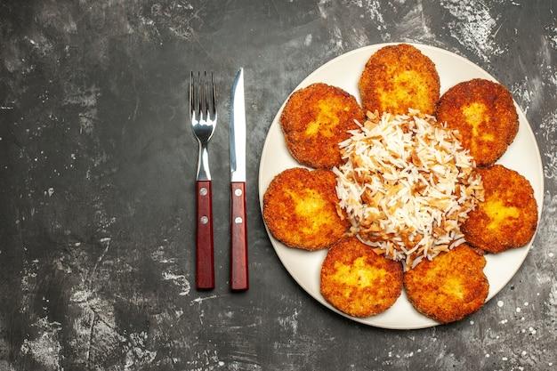 Bovenaanzicht smakelijke gebakken schnitzels met gekookte rijst op donkere vloer foto schotel maaltijd vlees