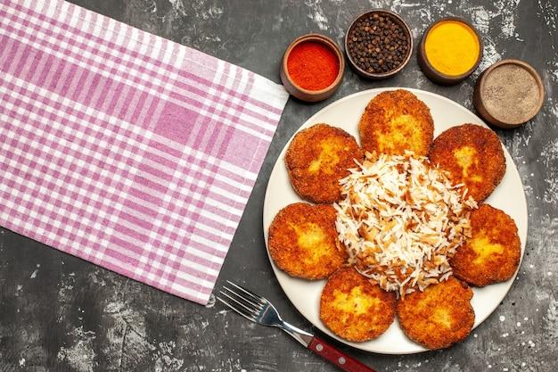 Bovenaanzicht smakelijke gebakken schnitzels met gekookte rijst op donkere vloer rissole vlees eten