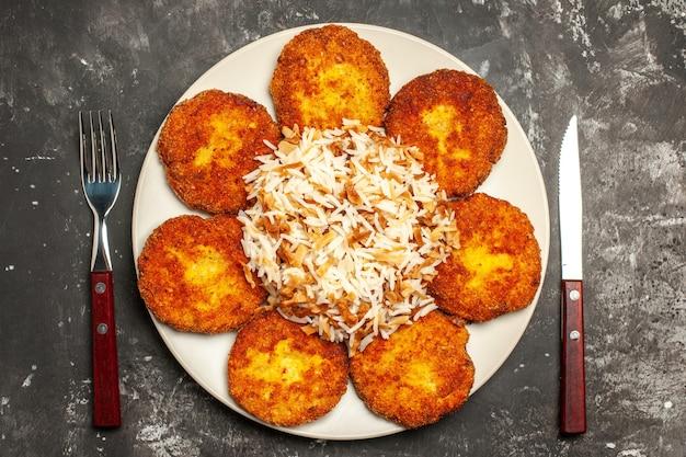 Bovenaanzicht smakelijke gebakken schnitzels met gekookte rijst op een donkere ondergrond foto schotel maaltijd vlees