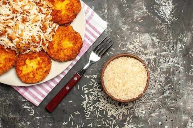 Bovenaanzicht smakelijke gebakken schnitzels met gekookte rijst op een donkere ondergrond rissole vleesgerecht