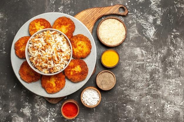 Bovenaanzicht smakelijke gebakken schnitzels met kruiderijen op vleesgerecht met donkere ondergrond