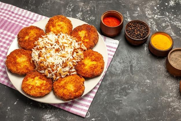 Bovenaanzicht smakelijke gebakken schnitzels met rijst en kruiden op donkere vloer eten vlees rissole
