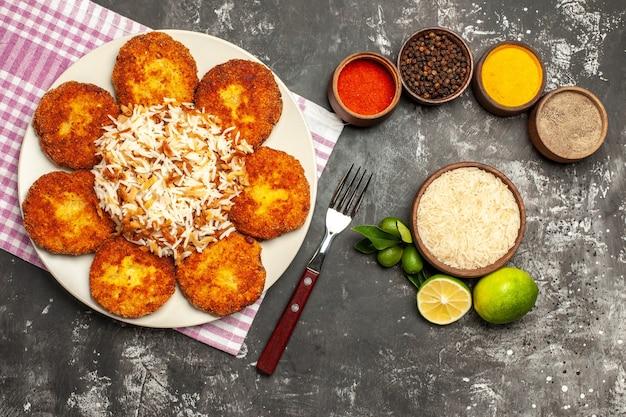 Bovenaanzicht smakelijke gebakken schnitzels met rijst en kruiden op het donkere oppervlak vlees rissole eten