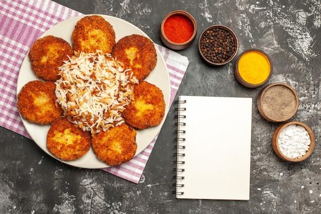 Bovenaanzicht smakelijke gebakken schnitzels met rijst en kruiderijen op donker bureau eten vlees rissole