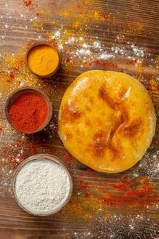 Bovenaanzicht smakelijke gebakken taart met smaakmakers op bruin houten bureau taart taart hotcake eten