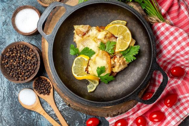 Bovenaanzicht smakelijke gebakken vis in pan op ronde houten plank cherrytomaatjes kruiden kommen houten lepels op grijze achtergrond