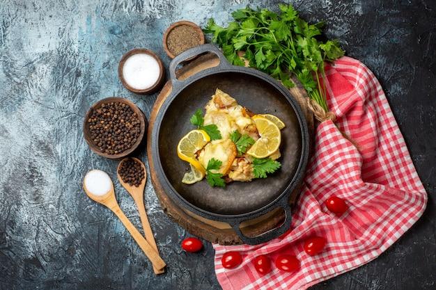 Bovenaanzicht smakelijke gebakken vis met citroen en peterselie in pan op houten bord