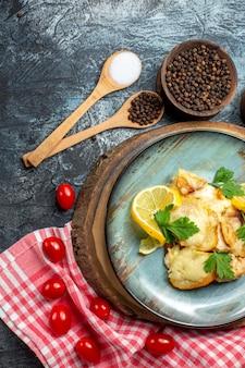 Bovenaanzicht smakelijke gebakken vis op plaat op houten bord cherrytomaatjes op rood en wit geruit tafelkleed kruiden in kommen houten lepels op grijze achtergrond