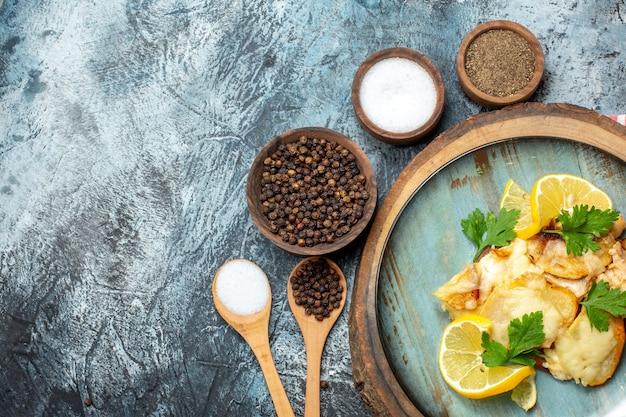 Bovenaanzicht smakelijke gebakken vis op plaat op houten bord verschillende kruiden in kommen houten lepels op grijze achtergrond